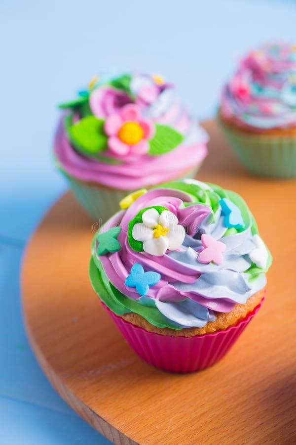 Tre bigné teneri con superiore multicolore cremoso decorati con i fiori variopinti e le farfalle sullo scrittorio rotondo di legn fotografie stock libere da diritti