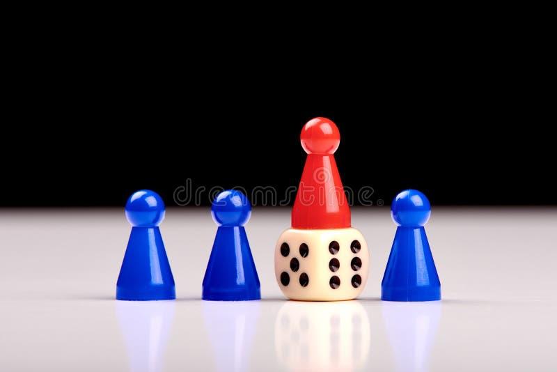 Tre blåa modiga stycken och dem emellan ställningar för ett röda stycke på tärning som en vinnare eller en ledare f?r kortdesign  royaltyfri fotografi
