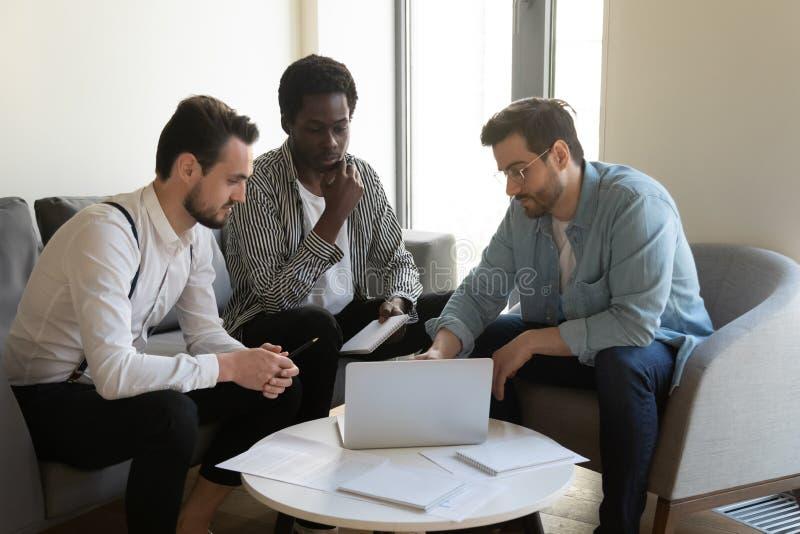 Tre blandras- affärsmän diskuterar online-projektblick på bärbara datorn arkivfoton