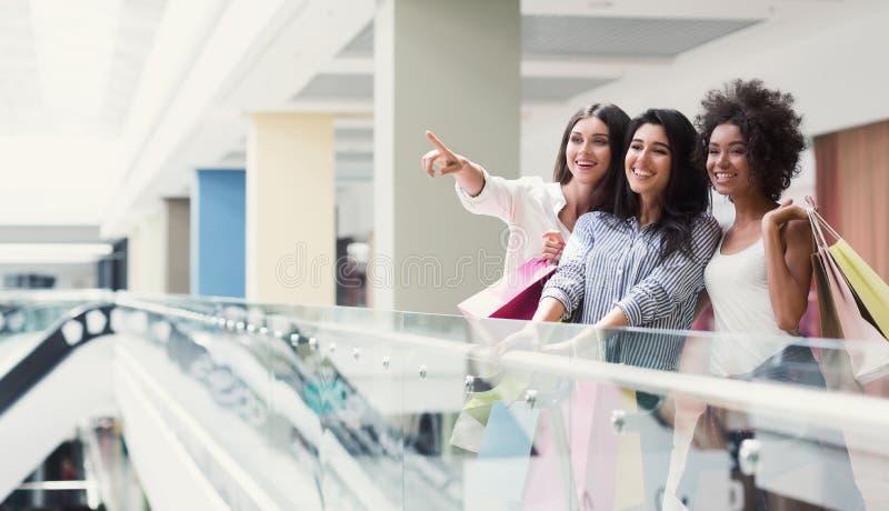 Tre blandras- flickor som pekar på något i galleria arkivfoto