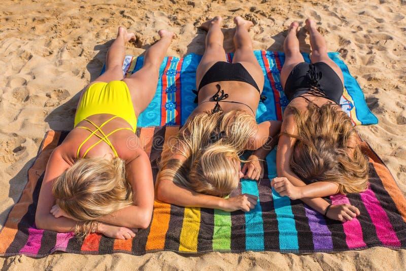 Tre blonda flickor som solbadar på stranden arkivbilder