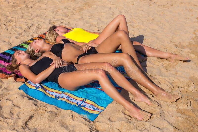 Tre blonda holländska flickor som solbadar på stranden royaltyfria bilder