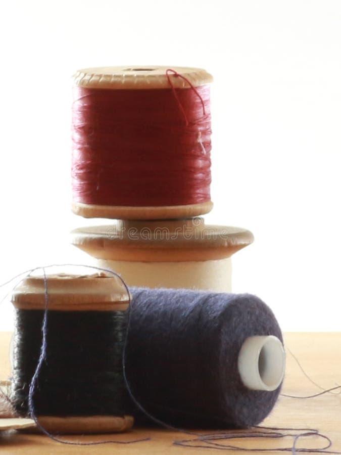 Tre bobine del cotone vicino su su una tavola con un fondo bianco fotografia stock