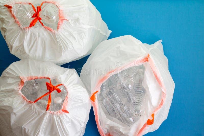 Tre borse bianche riempite di bottiglie di plastica fotografia stock libera da diritti