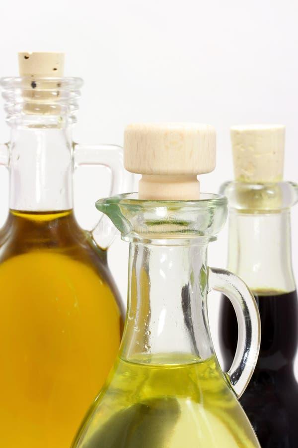 Tre bottiglie con olio immagini stock