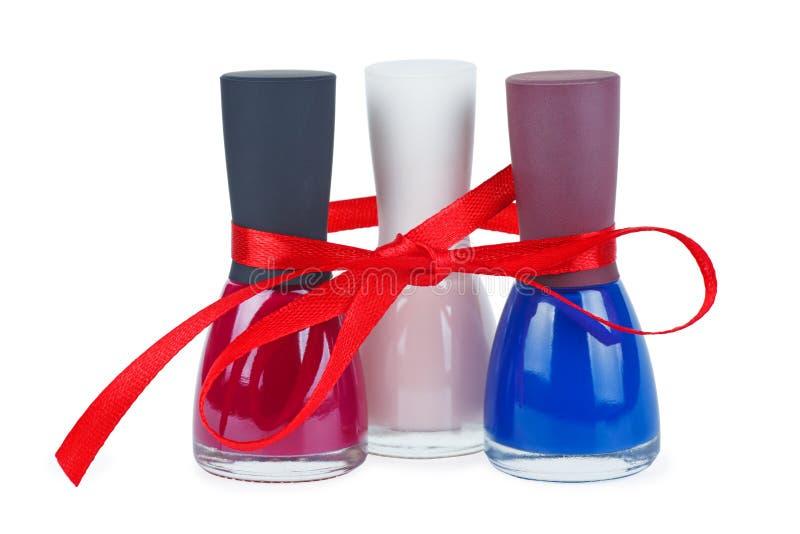 Tre bottiglie con smalto blu dei colori differenti legato con l'arco rosso fotografia stock libera da diritti
