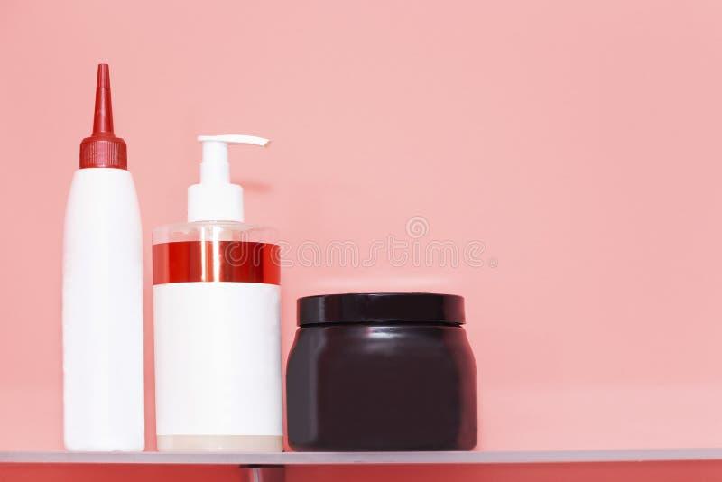 Tre bottiglie del gel della doccia o dello sciampo, erogatore crema su fondo colorato con lo spazio della copia fotografia stock