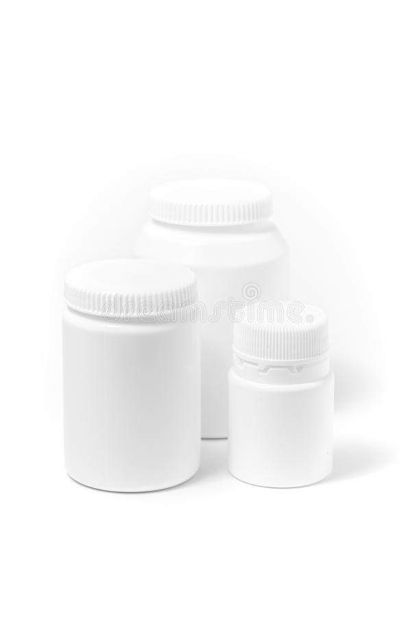 Tre bottiglie delle pillole bianche della medicina isolate su bianco fotografia stock