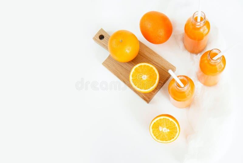 Tre bottiglie di fresco arancio e dei tubi sono sulla tavola su un wh immagine stock libera da diritti