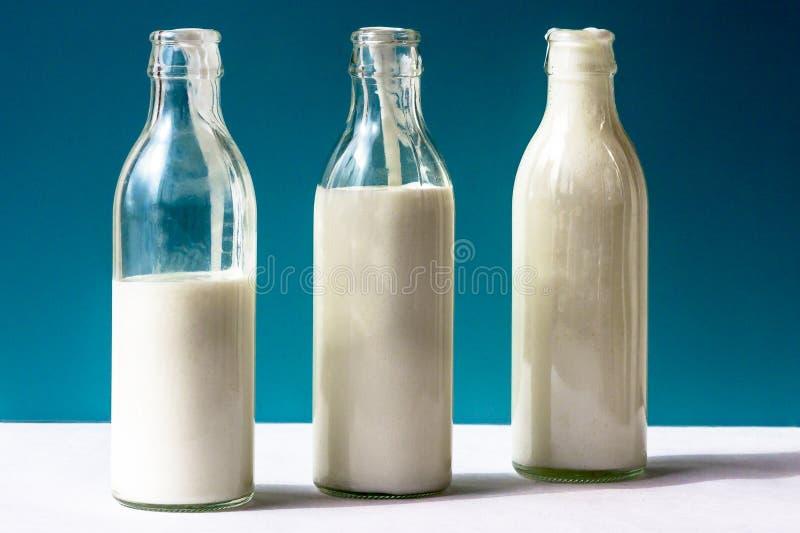 Tre bottiglie di vetro con il prodotto lattiero-caseario su un fondo blu immagini stock