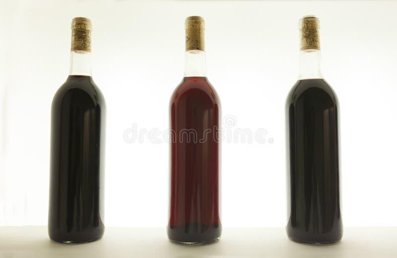 Tre bottiglie di vino rosso con differenti toni fotografie stock libere da diritti
