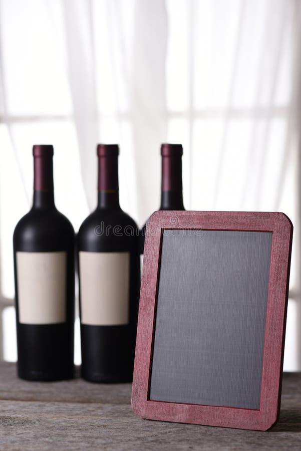 Tre bottiglie di vino rosso e del bordo di gesso in bianco fotografie stock libere da diritti