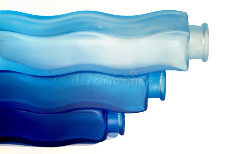 Tre bottiglie variopinte su priorità bassa bianca fotografia stock libera da diritti