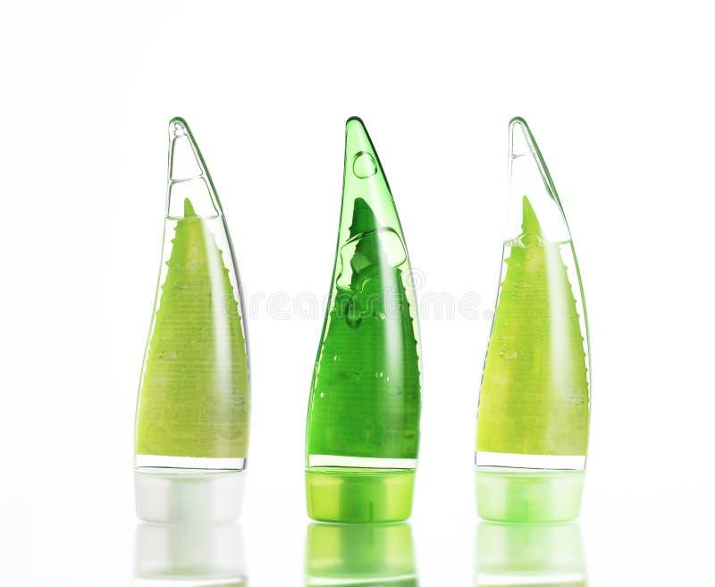 tre bottiglie verdi di trucco gel, sciampo e crema ecologici su fondo bianco isolato immagine stock