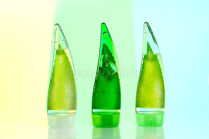 tre bottiglie verdi di trucco gel, sciampo e crema ecologici su un fondo verde chiaro isolato fotografia stock