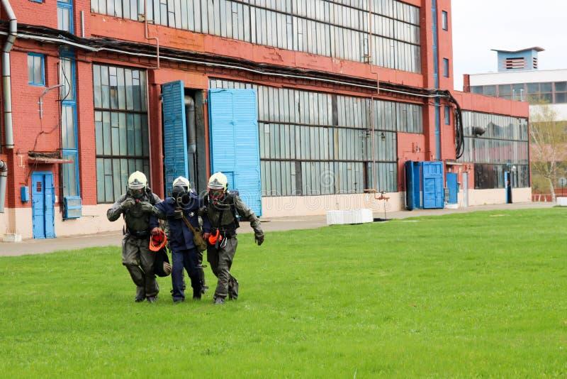 Tre brandmanräddare i skyddande brandsäkra dräkter och hjälmar tar den sårade personen i en gasmask från riskzonen in royaltyfri foto