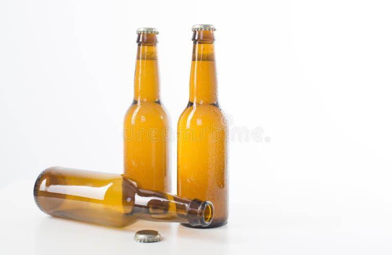Tre bruna ölflaskor arkivfoto
