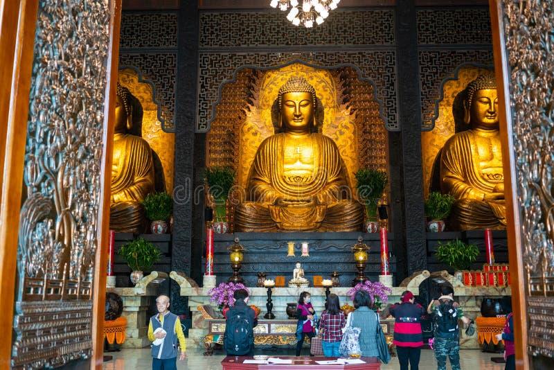 Tre Buddha e la gente che pregano al santuario principale di Sangha FO Guan fotografia stock
