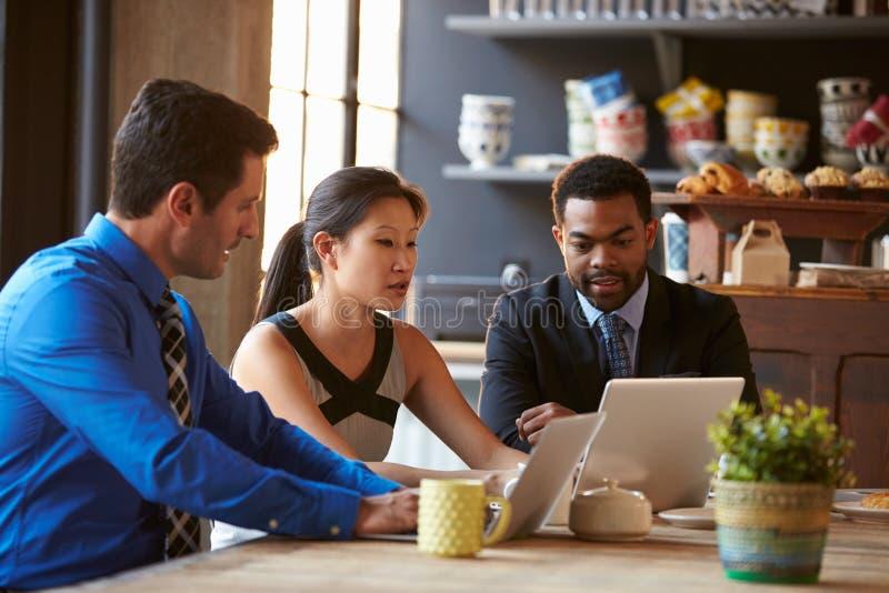 Tre Businesspeople som arbetar på bärbara datorn i kafé arkivbilder
