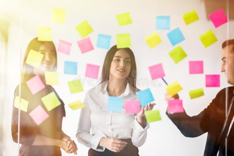 Tre businesspeople som diskuterar och planerar begrepp Framdel av glasväggmarkören och klistermärkear Startup kontor royaltyfria foton