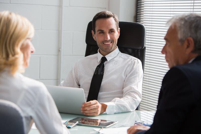 Tre businesspeople som har ett möte i kontoret royaltyfri bild
