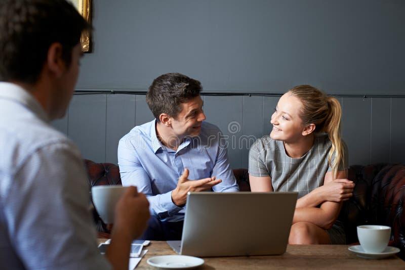 Tre Businesspeople som har möte i kafé arkivfoton