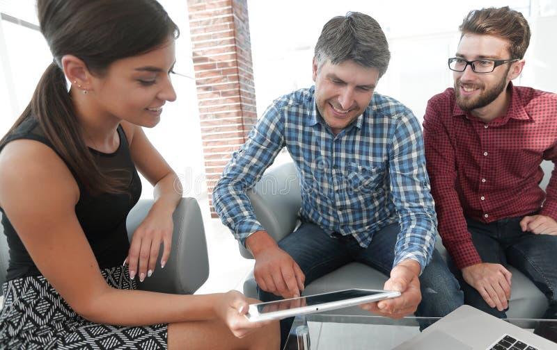 Tre businesspeople som i regeringsställning sitter lobbyen som ler och arbetar royaltyfria foton