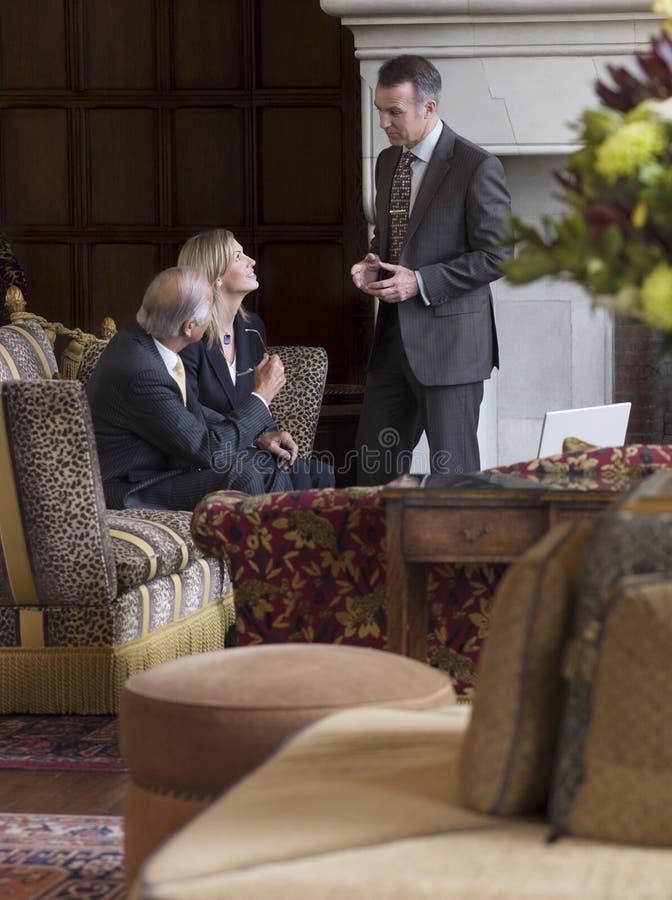 Tre Businesspeople som i regeringsställning talar lobbyen fotografering för bildbyråer