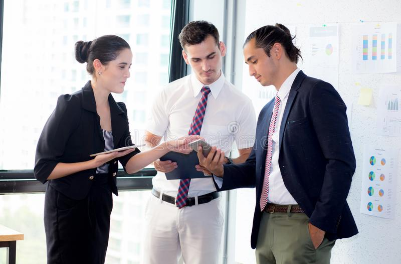 Tre businesspeople som står i det moderna kontoret som ser den smarta mobiltelefonen och talar i mötesrum royaltyfri fotografi