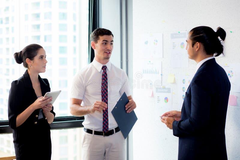 Tre businesspeople som står i det moderna kontoret som ser mappdokumentet och talar i mötesrum royaltyfri fotografi