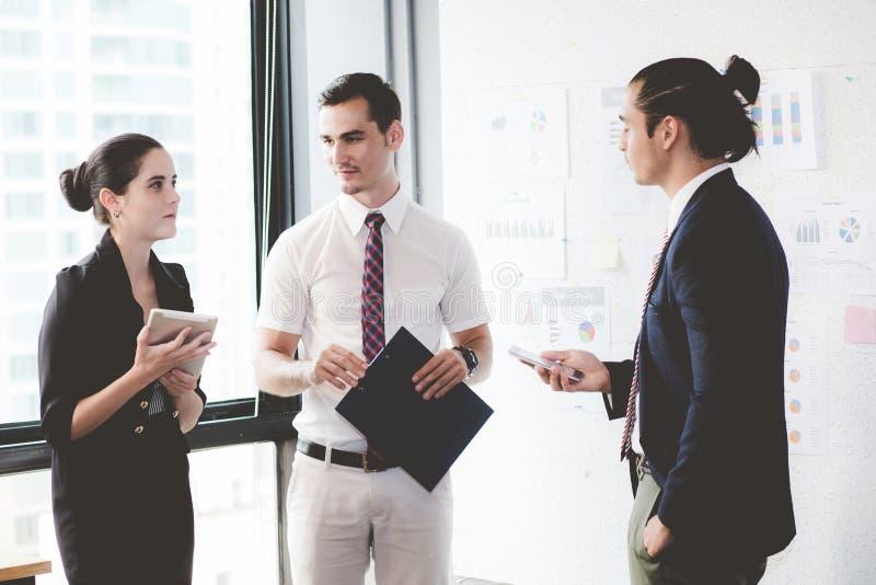Tre businesspeople som står i det moderna kontoret som ser mappdokumentet arkivfoto