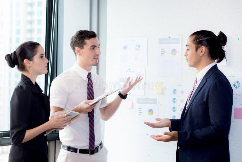 Tre businesspeople som står i det moderna kontoret som ser mappen som documeeting royaltyfria foton