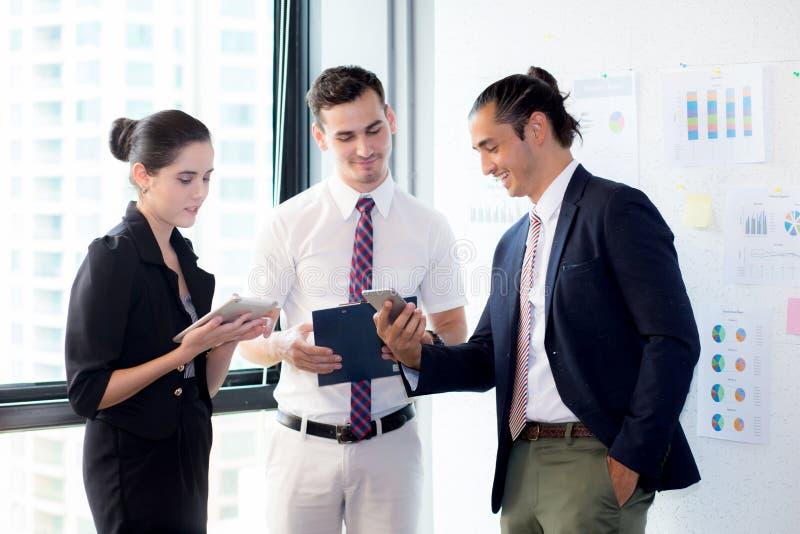 Tre businesspeople som står i det moderna kontoret som ser telefonen och talar möte arkivbild