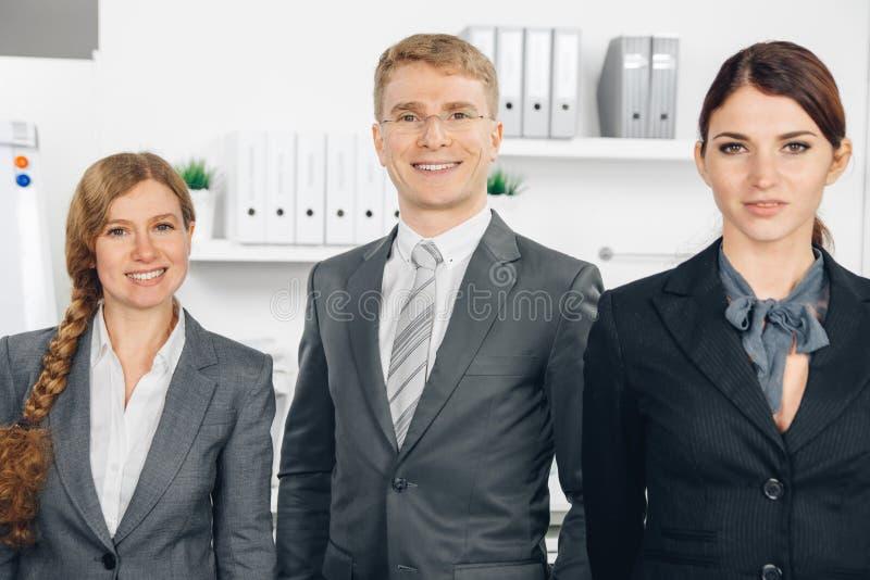 Tre businesspersons che stanno nella linea fotografia stock libera da diritti