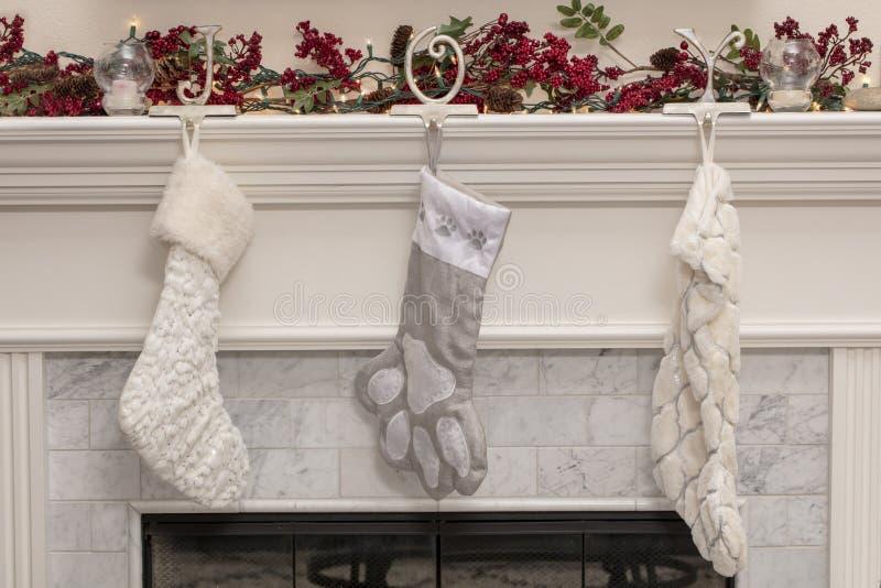 Tre calze di Natale su una mensola del camino del camino fotografia stock libera da diritti