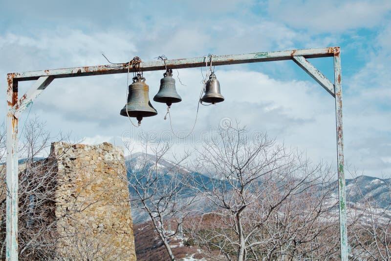 Tre campane e le rovine di un muro di mattoni vicino al Jvari Orthodo immagine stock libera da diritti
