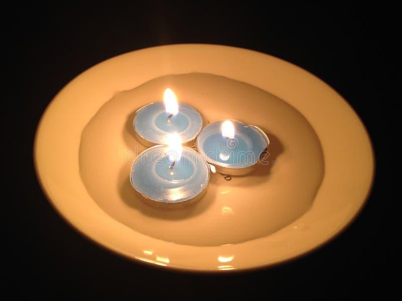 Tre candele blu brucianti in un piatto con acqua nello scuro Ea immagine stock