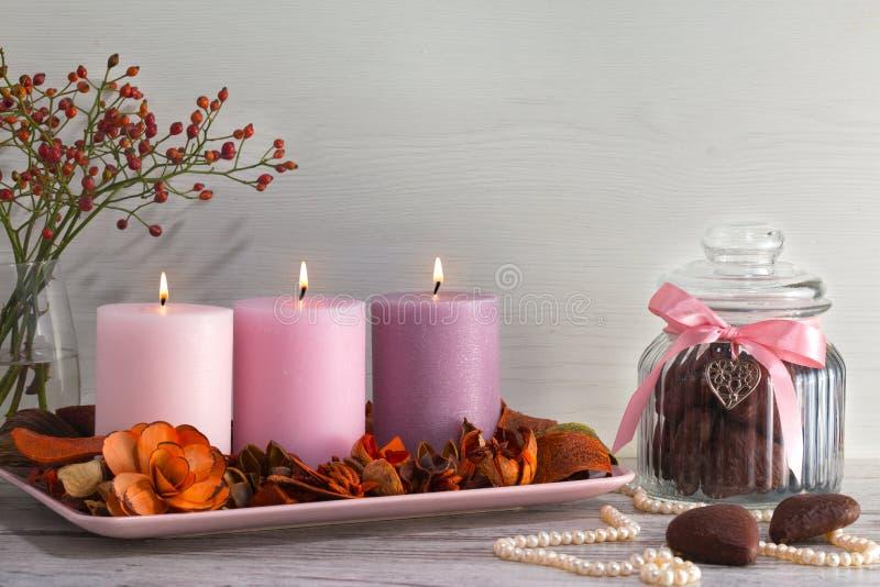 Tre candele brucianti sul supporto con i fiori e la corteccia decorativi asciutti Imperli la collana, il barattolo per i biscotti immagine stock libera da diritti