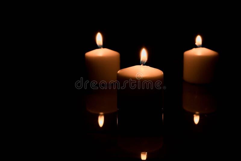 Tre candele dell'oro isolate sul nero con le riflessioni su una tavola di vetro nera fotografia stock
