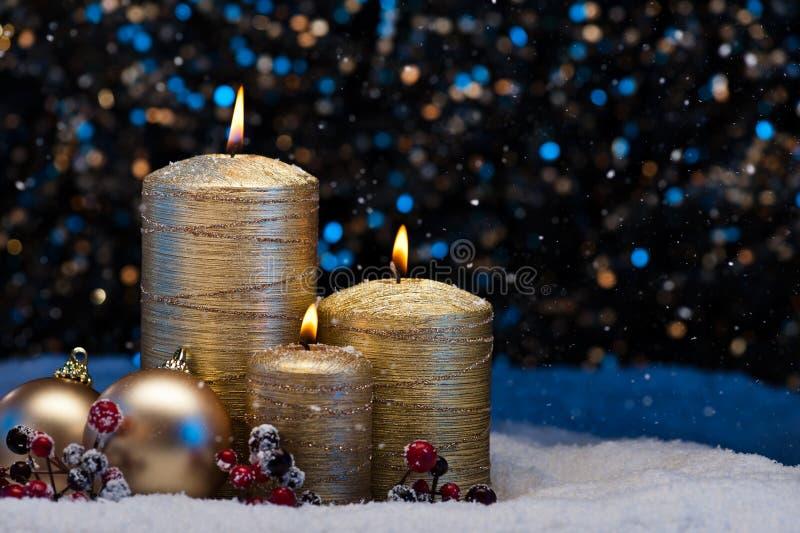 Tre candele dell'oro in neve immagine stock