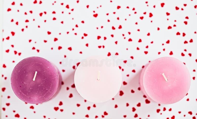 Tre candele rosa su un fondo hearted rosso immagine stock
