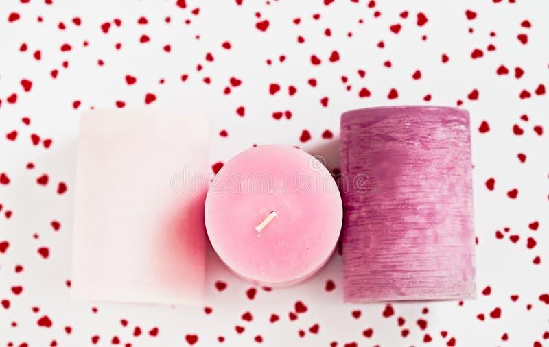 Tre candele rosa su un fondo hearted rosso immagine stock libera da diritti