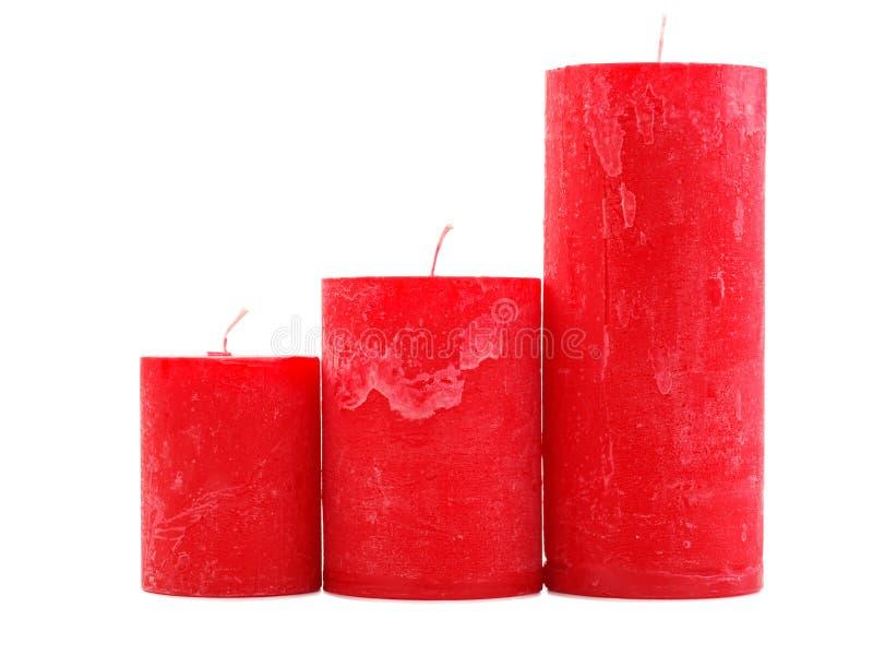 Tre candele rosse della cera della dimensione differente isolate su fondo bianco fotografia stock libera da diritti