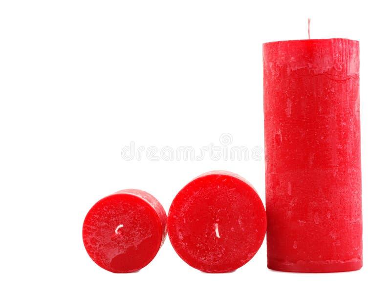 Tre candele rosse della cera della dimensione differente isolate su fondo bianco fotografie stock