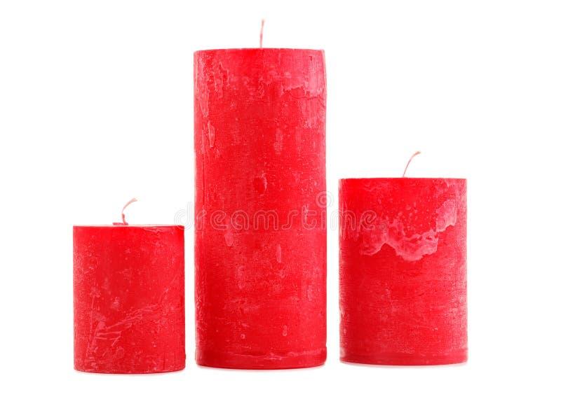Tre candele rosse della cera della dimensione differente isolate su fondo bianco immagine stock