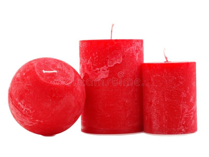Tre candele rosse della cera isolate su fondo bianco fotografia stock libera da diritti