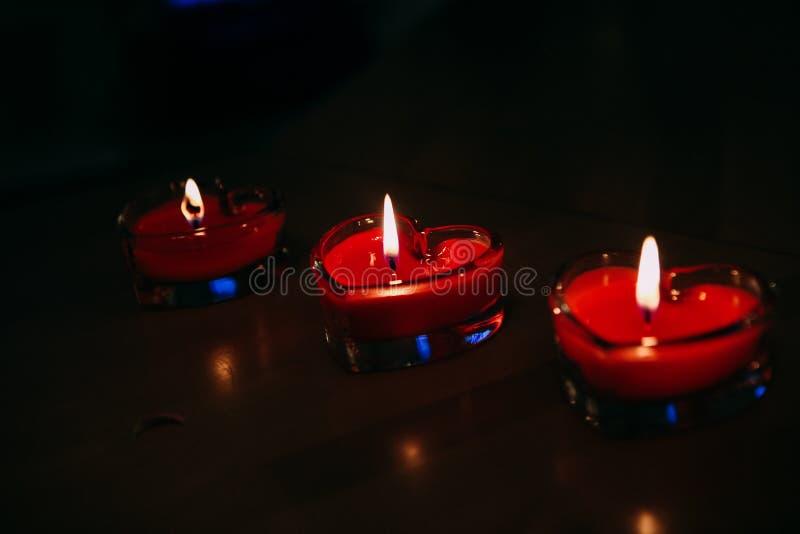 Tre candele sotto forma di ustione di cuore immagini stock