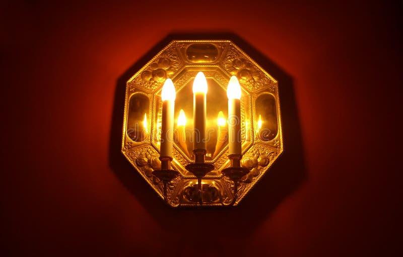 Download Tre candele su una parete immagine stock. Immagine di illuminazione - 3876919