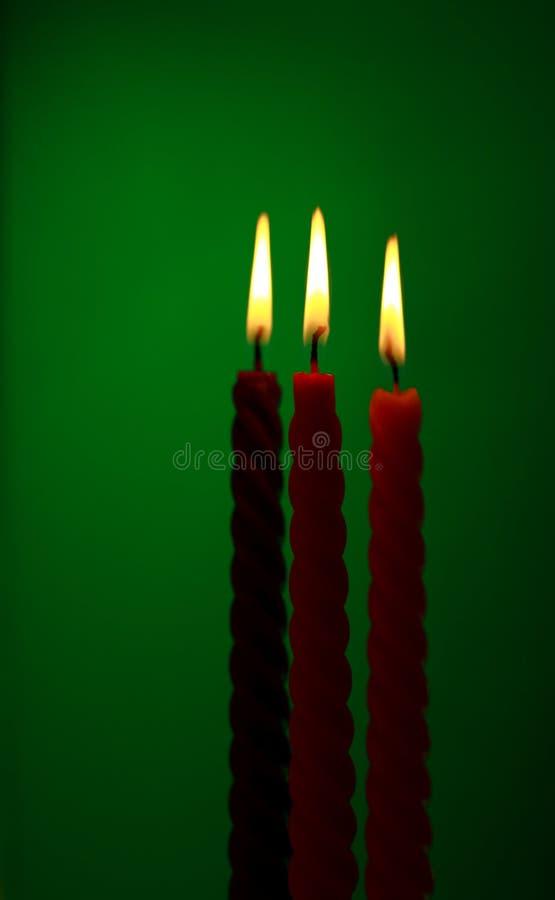 Tre candele su verde fotografia stock