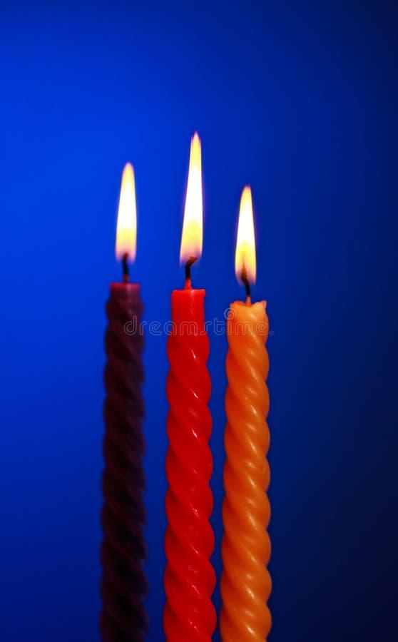 Tre candele sull'azzurro immagine stock libera da diritti